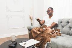 Młody amerykanin afrykańskiego pochodzenia mężczyzna, zakrywający z koc, ogląda TV w domu zdjęcia royalty free