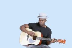 Młody amerykanina afrykańskiego pochodzenia mężczyzna bawić się gitarę nad bławym tłem Zdjęcia Stock