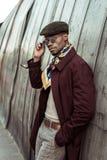Młody amerykanina afrykańskiego pochodzenia mężczyzna jest ubranym okulary przeciwsłonecznych i przypadkową odzież opiera, zdjęcie royalty free