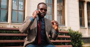 Młody amerykanina afrykańskiego pochodzenia mężczyzna obsiadanie na ławce i rozmowy na jego smartphone Opowiada jego partner bizn zbiory wideo