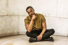 Młody amerykanina afrykańskiego pochodzenia mężczyzna obsiadanie na ziemi w Nowy Jork, thinki Obrazy Royalty Free