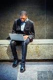 Młody amerykanina afrykańskiego pochodzenia mężczyzna pracuje na laptopie outside wewnątrz zdjęcia stock