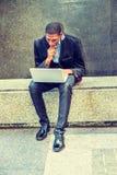 Młody amerykanina afrykańskiego pochodzenia mężczyzna pracuje na laptopie outside wewnątrz zdjęcie royalty free