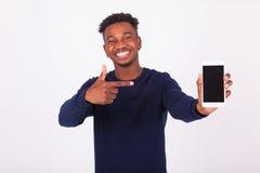 Młody amerykanina afrykańskiego pochodzenia mężczyzna wskazuje jego smartphone ekran - Bla Zdjęcia Stock