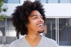 Młody amerykanina afrykańskiego pochodzenia mężczyzna z afro roześmianym outside Obrazy Stock