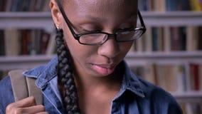 Młody amerykanina afrykańskiego pochodzenia uczeń w szkło czytelniczej książce i ono uśmiecha się przy kamerą, półka na książki w zbiory wideo