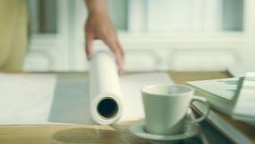 Młody architekt lub projektant rozwija się rolkę brulionowość papier zdjęcie wideo