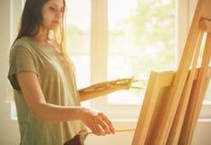Młody artysty obraz na sztaludze obraz stock