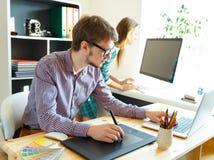 Młody artysty rysunek coś na graficznej pastylce przy biurem Obraz Royalty Free