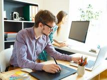 Młody artysty rysunek coś na graficznej pastylce przy biurem Zdjęcie Royalty Free