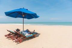 Młody Asain mężczyzna podróżnika lying on the beach na plażowej ławce Obrazy Royalty Free