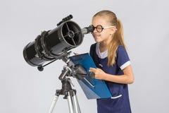 Młody astronom szczęśliwy patrzeć przez teleskop magnetofonowych obserwacj Zdjęcia Royalty Free