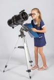 Młody astronom w szkłach z interesem ono przygląda się w eyepiece teleskop Obraz Royalty Free