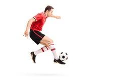 Młody atlety doskakiwanie, kopanie i futbol obraz stock