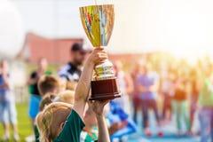 Młody atlety mienia trofeum Młodość sporta piłki nożnej drużyna z trofeum Zdjęcie Royalty Free