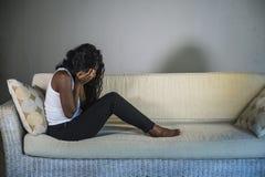 Młody atrakcyjnego i smutnego czarnego afrykanina kobiety Amerykański obsiadanie deprymował w domu kanapy leżanki uczucia niespok obraz stock