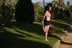 Młody atrakcyjny żeński biegacz robi rozciągania ćwiczeniu w pięknym zieleń parku Zdjęcia Stock
