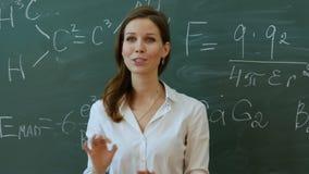 Młody atrakcyjny żeński nauczyciel oddziała wzajemnie z jej młodymi szkoła podstawowa uczniami pyta dla odpowiedzi maths zbiory