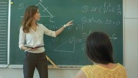 Młody atrakcyjny żeński nauczyciel oddziała wzajemnie z jej młodymi szkoła podstawowa uczniami pyta młodej dziewczyny dla maths zdjęcie wideo