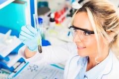 Młody atrakcyjny żeński naukowiec egzamininuje próbnej tubki z śliwki zdjęcia stock