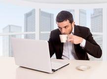 Młody atrakcyjny biznesmen pracuje przy dzielnicy biznesu biurowym obsiadaniem przy komputerowym biurkiem pije kawę obraz royalty free