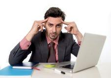 Młody atrakcyjny biznesmena obsiadanie przy biurowym biurkiem pracuje na komputerowej laptopu cierpienia migrenie Obraz Stock