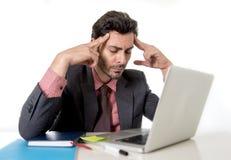 Młody atrakcyjny biznesmena obsiadanie przy biurowym biurkiem pracuje na komputerowej laptopu cierpienia migrenie Fotografia Royalty Free