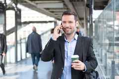 Młody atrakcyjny biznesowy mężczyzna używa smartphone podczas gdy pijący co zdjęcia royalty free