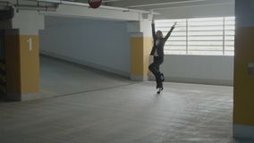 Młody atrakcyjny bizneswoman jest ubranym formalnego kostiumu doskakiwanie i śmiesznego tana w podziemnym parking na jej sposobie zdjęcie wideo