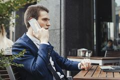 Młody atrakcyjny brunetka biznesmen opowiada telefonem komórkowym w kawiarni fotografia stock