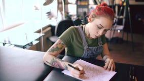 Młody atrakcyjny czerwony z włosami kobieta tatuażu artysty obsiadanie przy stołowym i tworzy nakreśleniem dla tatuować w studiu  zbiory wideo