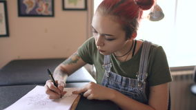 Młody atrakcyjny czerwony z włosami kobieta tatuażu artysty obsiadanie przy stołowym i tworzy nakreśleniem dla tatuować w studiu  zbiory
