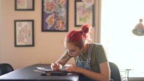 Młody atrakcyjny czerwony z włosami kobieta tatuażu artysty obsiadanie przy stołowym i tworzy nakreśleniem dla tatuować w studiu  zdjęcie wideo