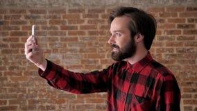 Młody atrakcyjny facet z brodą mówi w videochat na smartphone online, komunikacyjny pojęcie, ceglany tło zbiory wideo