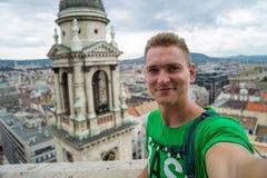 Młody atrakcyjny facet z niebieskimi oczami bierze selfie na odgórnego widoku punkcie z Budapest na tle obraz royalty free