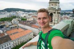 Młody atrakcyjny facet z niebieskimi oczami bierze selfie na odgórnego widoku punkcie z Budapest na tle zdjęcia stock