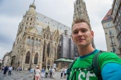 Młody atrakcyjny facet z niebieskimi oczami bierze selfie z ogromnym kościół na tle w Europe zdjęcie stock