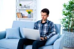 Młody atrakcyjny faceta mężczyzna wyszukuje przy jego laptopem, siedzi w domu na wygodnej błękitnej kanapie w domu, będący ubrany obrazy royalty free