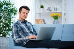 Młody atrakcyjny faceta mężczyzna wyszukuje przy jego laptopem, siedzi w domu na wygodnej błękitnej kanapie w domu, będący ubrany obraz royalty free