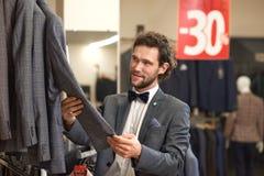 Młody atrakcyjny fornal w popielatej kostiumowej mienie kurtce zdjęcia royalty free