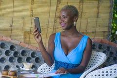 Młody atrakcyjny i szczęśliwy czarny afro amerykański biznesowej kobiety pracować relaksował od pięknego sklep z kawą używać tele Obrazy Stock