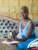 Młody atrakcyjny i szczęśliwy czarny afro Amerykański biznesowej kobiety pracować relaksował od pięknego sklep z kawą używać tele Fotografia Stock
