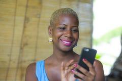 Młody atrakcyjny i szczęśliwy czarny afro amerykański biznesowej kobiety pracować relaksował od pięknego sklep z kawą używać tele Obraz Stock