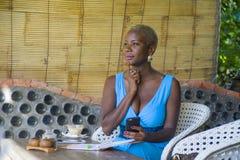 Młody atrakcyjny i szczęśliwy czarny afro amerykański biznesowej kobiety pracować relaksował od pięknego sklep z kawą używać tele Zdjęcie Stock