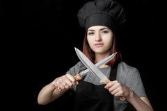 Młody atrakcyjny kobieta szef kuchni w czerń mundurze trzyma Dwa noża na czarnym tle Ostrość na nożach obrazy stock