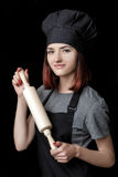 Młody atrakcyjny kobieta szef kuchni w czerń mundurze trzyma tocznej szpilki na czarnym tle fotografia royalty free