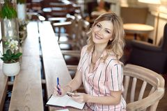 Młody atrakcyjny kobiety freelancer obsiadanie przy stołem z notepad i smartphone zdjęcie stock