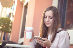 Młody atrakcyjny kobiety mienia telefon komórkowy i filiżanka kawy Obraz Royalty Free