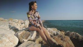Młody atrakcyjny kobiety obsiadanie na skała kamieniu patrzeje w odległość na zmierzch górach dennego wybrzeża tle i zdjęcie wideo