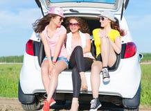 Młody atrakcyjny kobiety obsiadanie w otwartym bagażniku Zdjęcie Stock